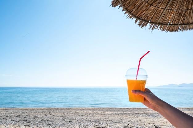ビーチの傘の下で飲み物とカップを持っている女性の手