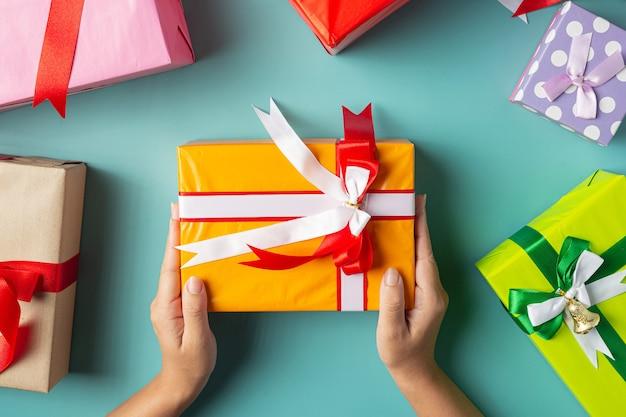 Женская рука держит подарочную коробку на светло-зеленом полу