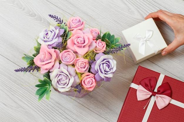 회색 나무 배경 위에 선물 상자를 들고 있는 여성의 손에는 장미 모양의 비누가 있습니다. 휴일에 선물을 주는 개념. 평면도.