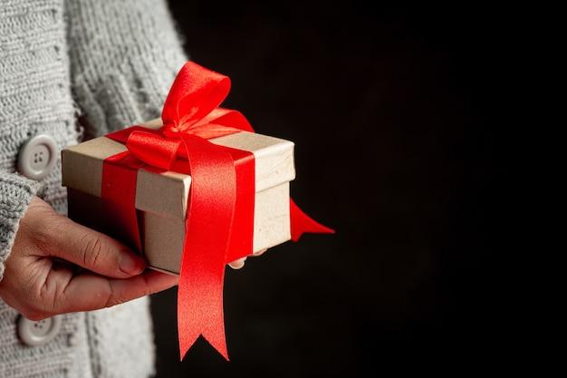 Женская рука держит подарочную коробку с красной лентой