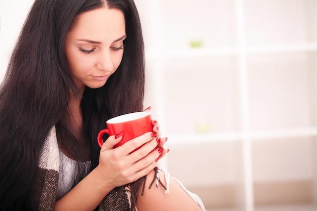 コーヒーの赤いカップを持っている女性の手。美しい冬のマニキュア付き。飲み物、ファッション、朝
