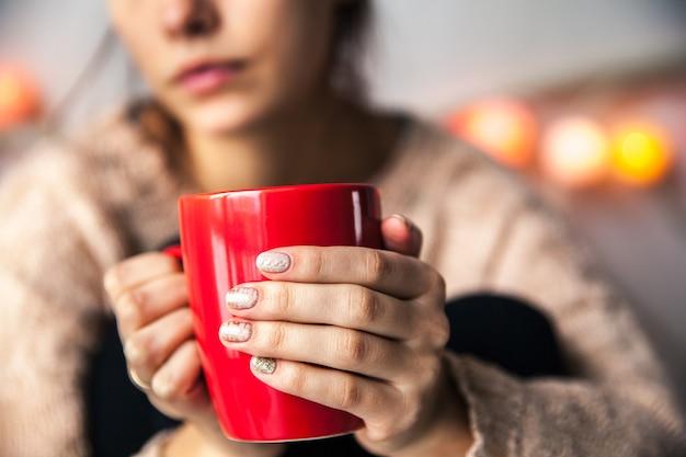 コーヒーの赤いカップを持っている女性の手。美しい冬のマニキュア付き。