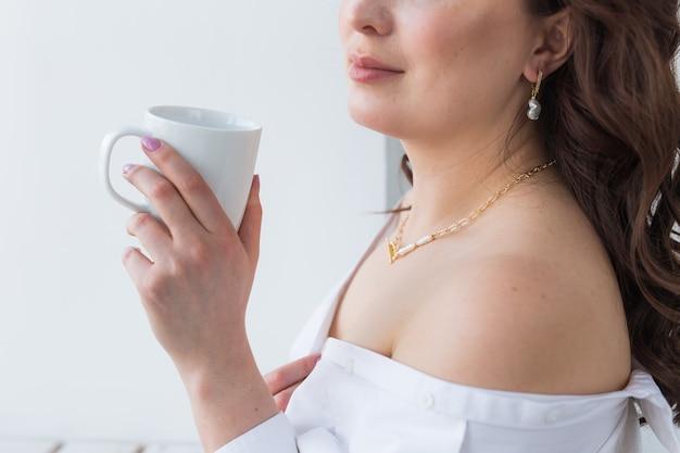 コーヒーの白いカップを持っている女性の手。美しいマニキュアのクローズアップ付き。飲み物、ファッション