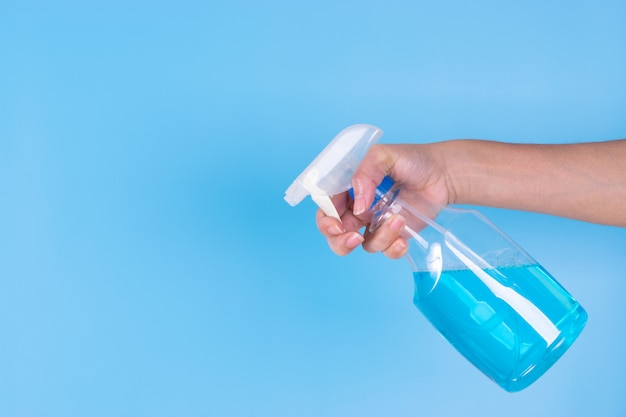 Woman's hand holding alcohol spray on blue sky background. spraying sanitizer to prevent covid-19.