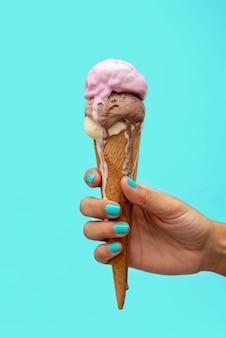 水色に溶けるアイスクリームコーンを持っている女性の手