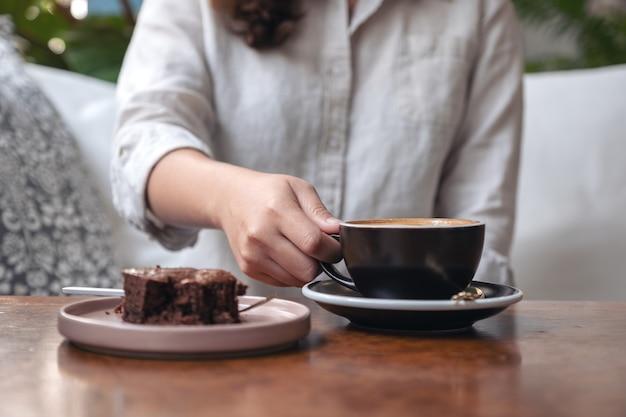 テーブルの上にブラウニーケーキとホットラテコーヒーを持って飲む女性の手