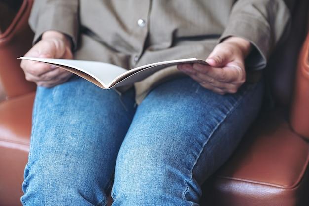 빈티지 소파에 앉아있는 동안 여자의 손을 잡고 빈 노트북을 여는