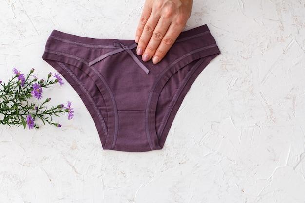 白い構造の背景に美しい紫色の綿のパンティーを持っている女性の手。女性下着セット。上面図。