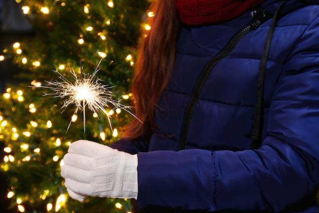 クリスマスツリーにベンガルの光を持っている女性の手