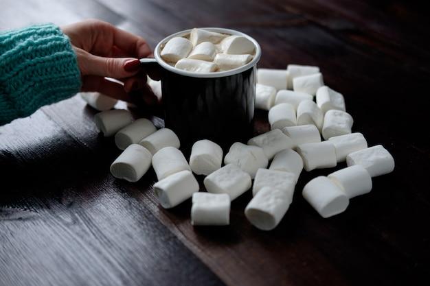 木製の暗い表面にマシュマロの間でマシュマロとコーヒーの黒いカップを持っている女性の手