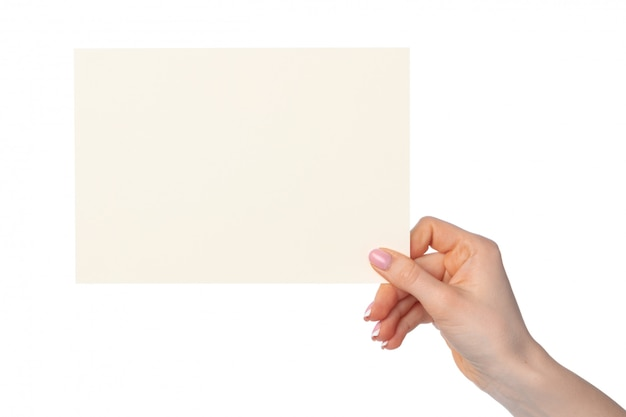 Woman's hand holding blank white sheet of paper isolated on white