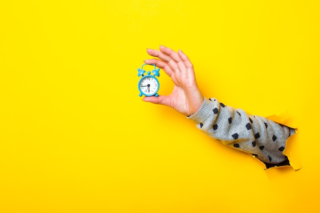 Woman's hand holding blue alarm clock on torn yellow background.