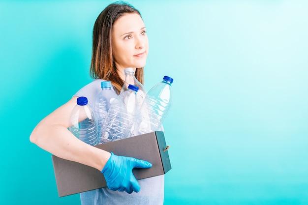 リサイクル用のペットボトルが入った女性の手持ちボックス。リサイクルの概念。環境への配慮