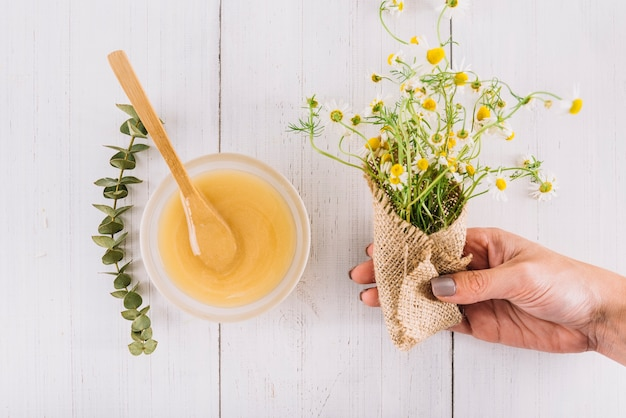 Woman's hand holding bunch of chamomile flowers near bowl of lemon curd