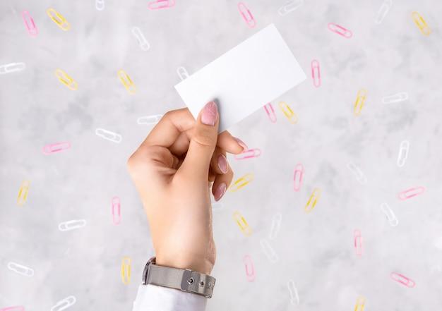 コンクリートの灰色の背景にビジネスカードを持っている女性の手。学校の仕事教育に戻るクリエイティブなレイアウト