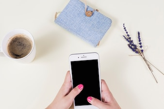 Woman's hand holding cell phone with coffee cup; diary and lavender on background