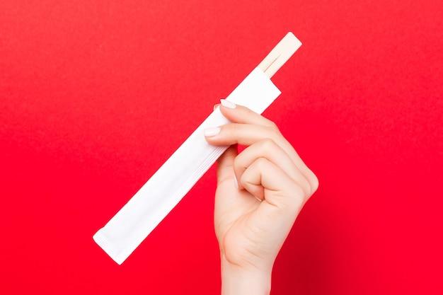 Женская рука палочки для еды в пачке на красном фоне. концепция китайской кухни с пустым пространством для вашего дизайна.