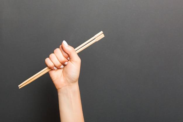 Женская рука палочками на черном фоне. концепция китайской кухни с пустым пространством для вашего дизайна.