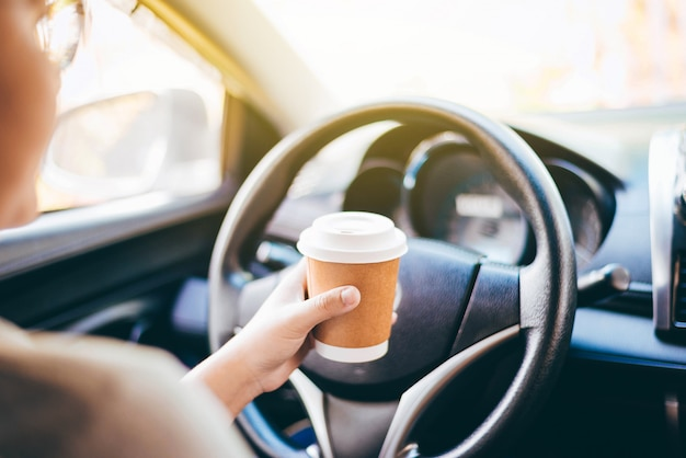 Woman's hand holding a coffee cup to take away, she is driving in the morning.