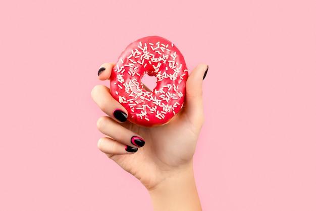 ピンクの表面にカラフルなドーナツを持っている女性の手