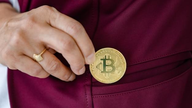 Женская рука держит крипто монету и кладет в карман. концепция инвестиций в цифровые активы и криптовалюту.