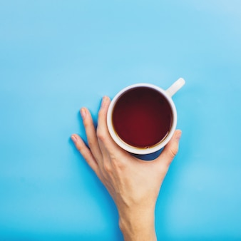 Woman's hand holding cup of hot tea or coffee