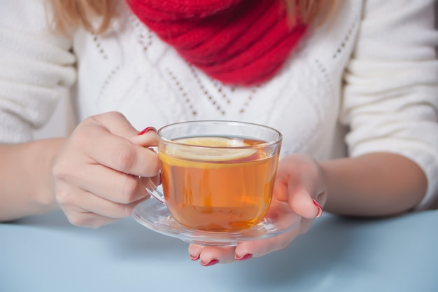 Woman's hand holding cup of tea with piece of lemon