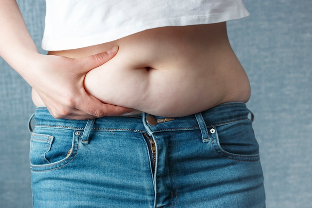 Woman's hand holding excessive belly fat, overweight concept