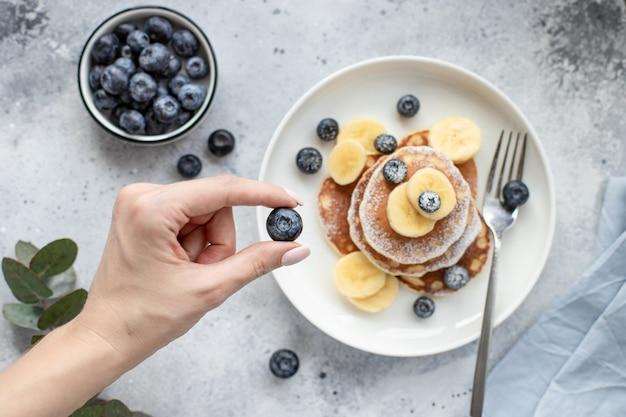 パンケーキとテーブルに新鮮なブルーベリーを持っている女性の手。水平方向の画像、上面図