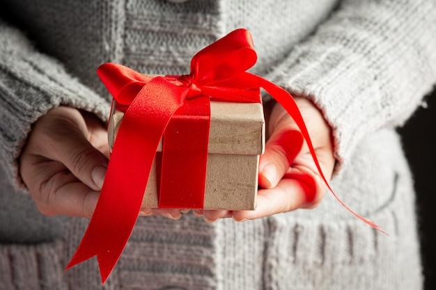 Mano della donna che tiene una confezione regalo con nastro rosso