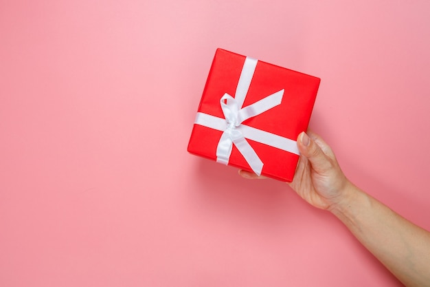 Woman's hand holding gift wrapped and decorated with bow