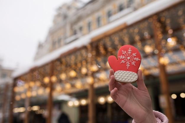 ボケ味を背景にクリスマスフェアでジンジャーブレッドを持っている女性の手