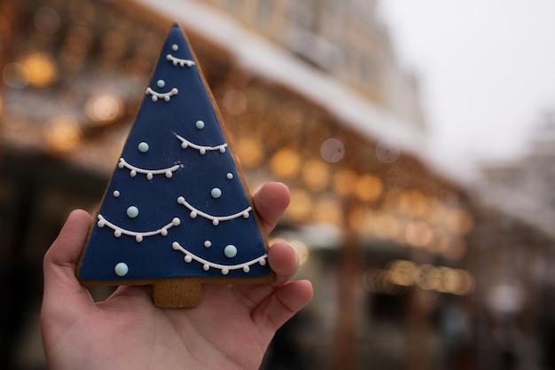 ボケ味を背景にクリスマスフェアでジンジャーブレッドのクッキーを持っている女性の手