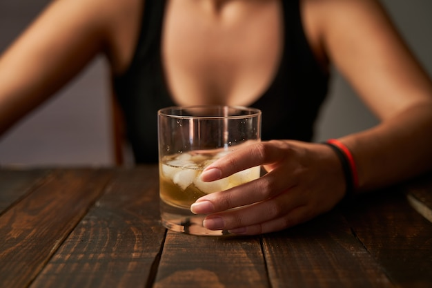 Woman's hand holding a glass of alcohol. concept of alcoholism and addictions.