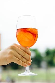 路上で夏にアルコール飲料のガラスを持っている女性の手。通りのテラスでコンセプトドリンク