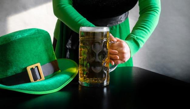 黒のレプラコーンの聖パトリックの日の帽子の近くでビールのガラスを持っている女性の手