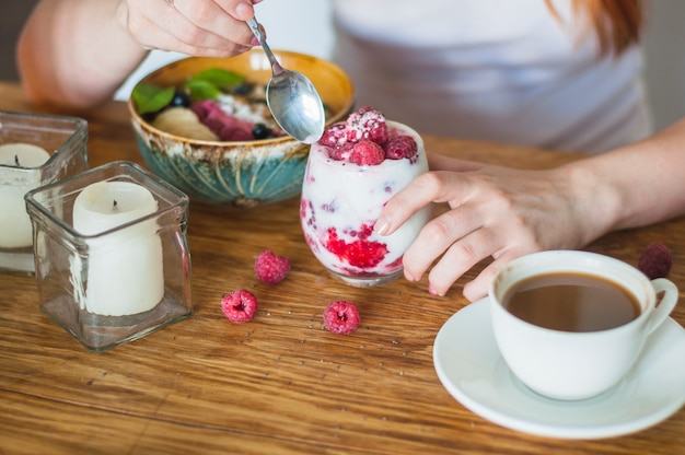 Woman's hand holding glass of yogurt with raspberries
