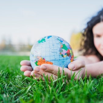 Woman's hand holding globe over green grass
