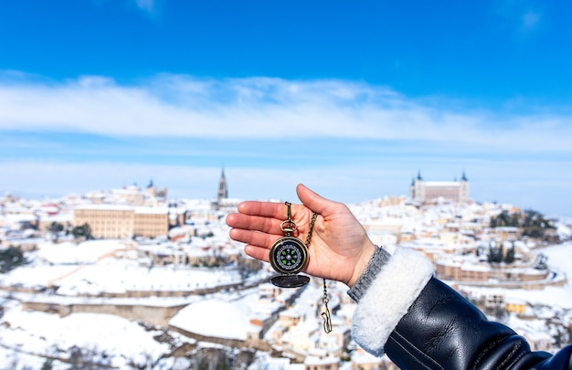 Woman's hand holding a gold compass. panoramic snowy view of the city of toledo in the background.