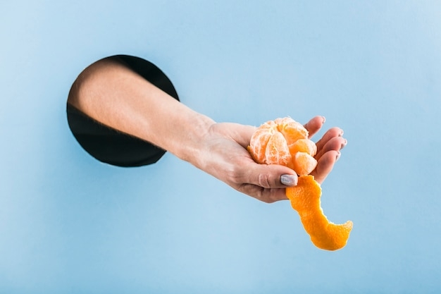 Woman's hand holding a half-peeled tangerine out of a black hole in a blue paper wall.
