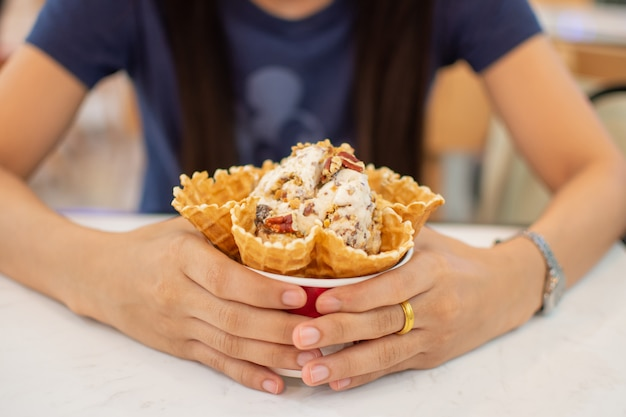 Woman's hand holding ice cream cup. soft focus.