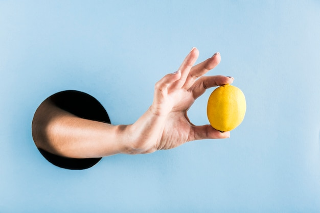 Woman's hand holding a lemon out of a black hole in a blue paper wall.