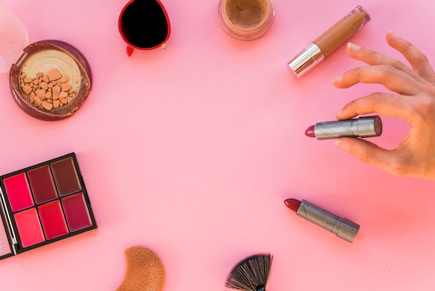 Woman's hand holding lipstick and various make up accessories on pink background