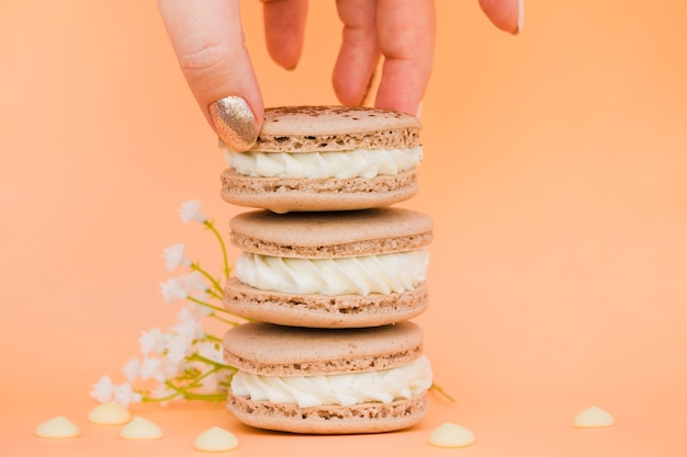 Woman's hand holding macaroons with flower against colored background