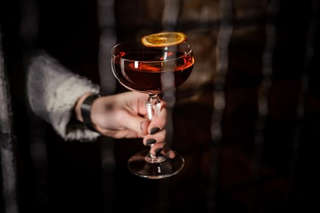 Woman's hand holding a manhattan cocktail