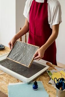 木製の机の上にパルプと型を保持している女性の手