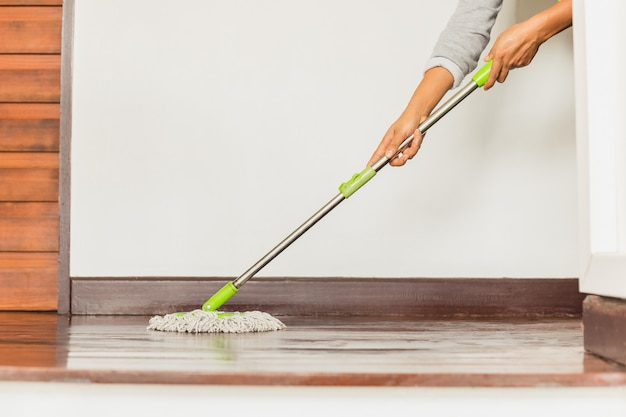 Woman's hand holding a mop cleaning house floor.