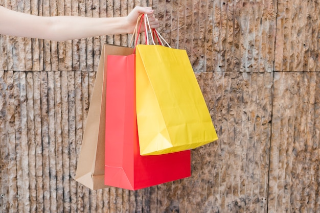 Woman's hand holding multi colored shopping bags