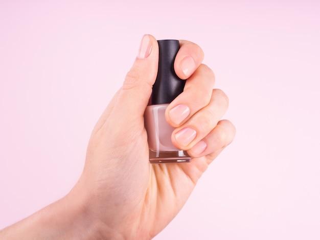 Woman's hand holding nude nail varnish