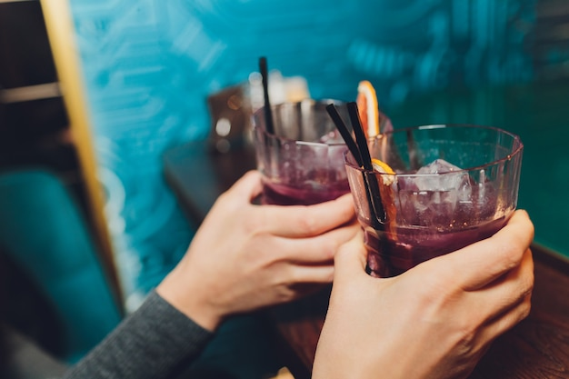 Woman's hand holding old fashioned glass with cold cocktail against blurred night club background.